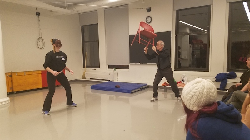 Jim Calder throwing a red chair to a student wearing a Commedia mask.