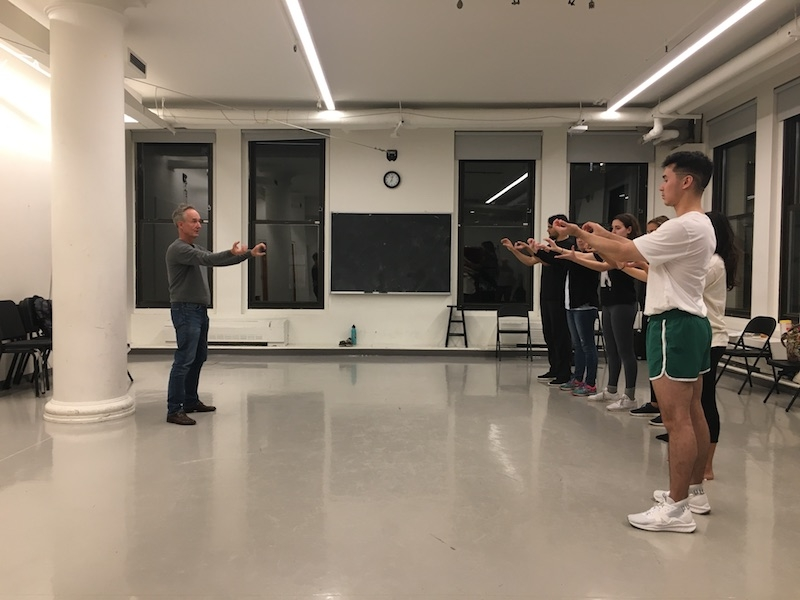 Jacob Oleson holding his arms like he is holding a stick, leading a miming exercise with the workshop attendees.