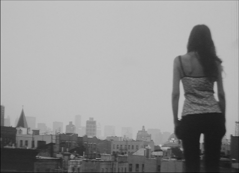 Woman standing with back to camera, looking out at a city skyline