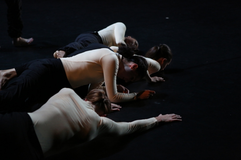 Dancers crawling across a stage