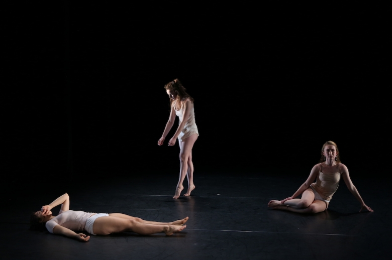 Three women dancers: one lying on the stage, one on pointe, and the third seated, looking at the audience.