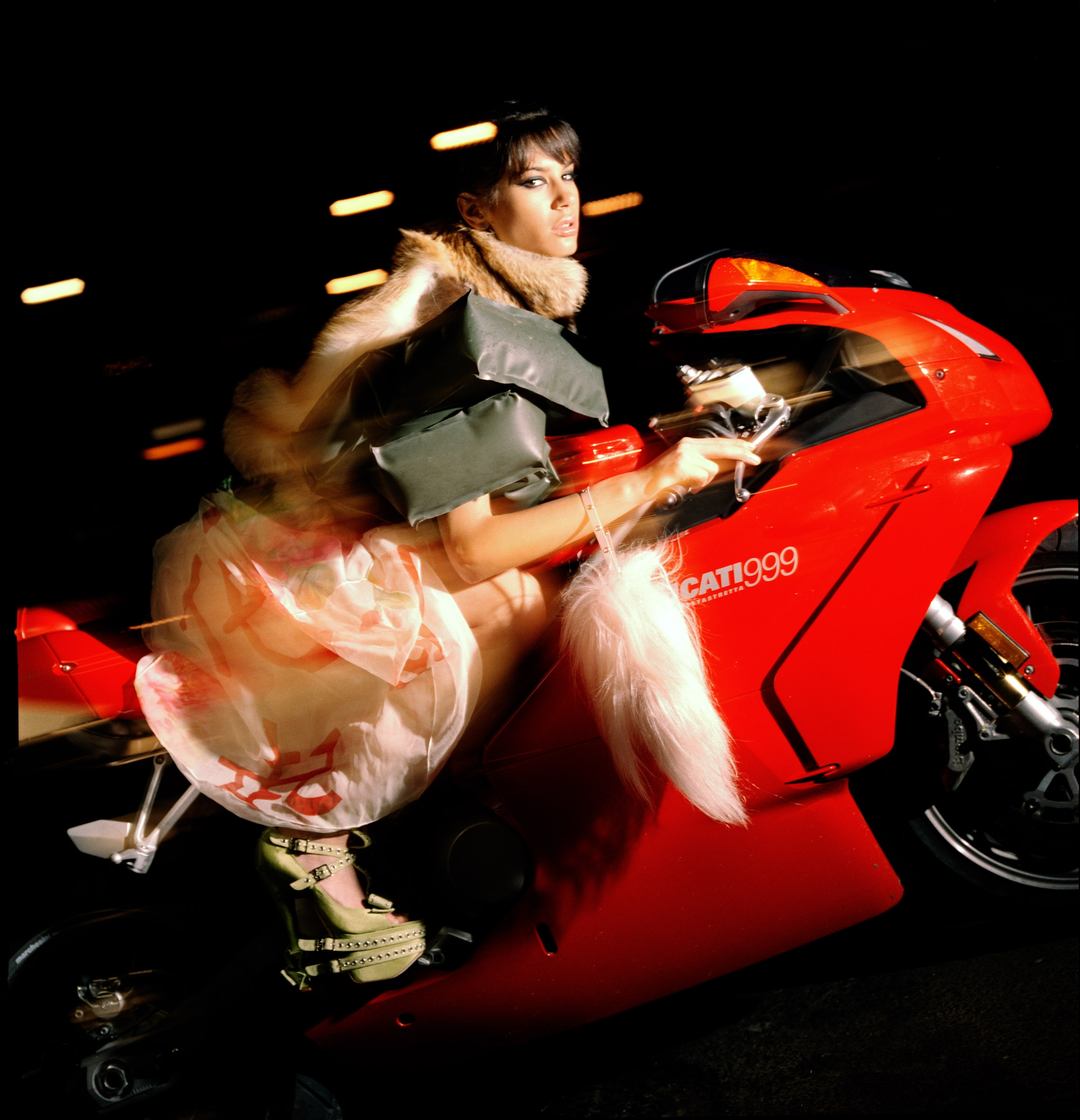 Action shot of a model posed on a red motorcycle.
