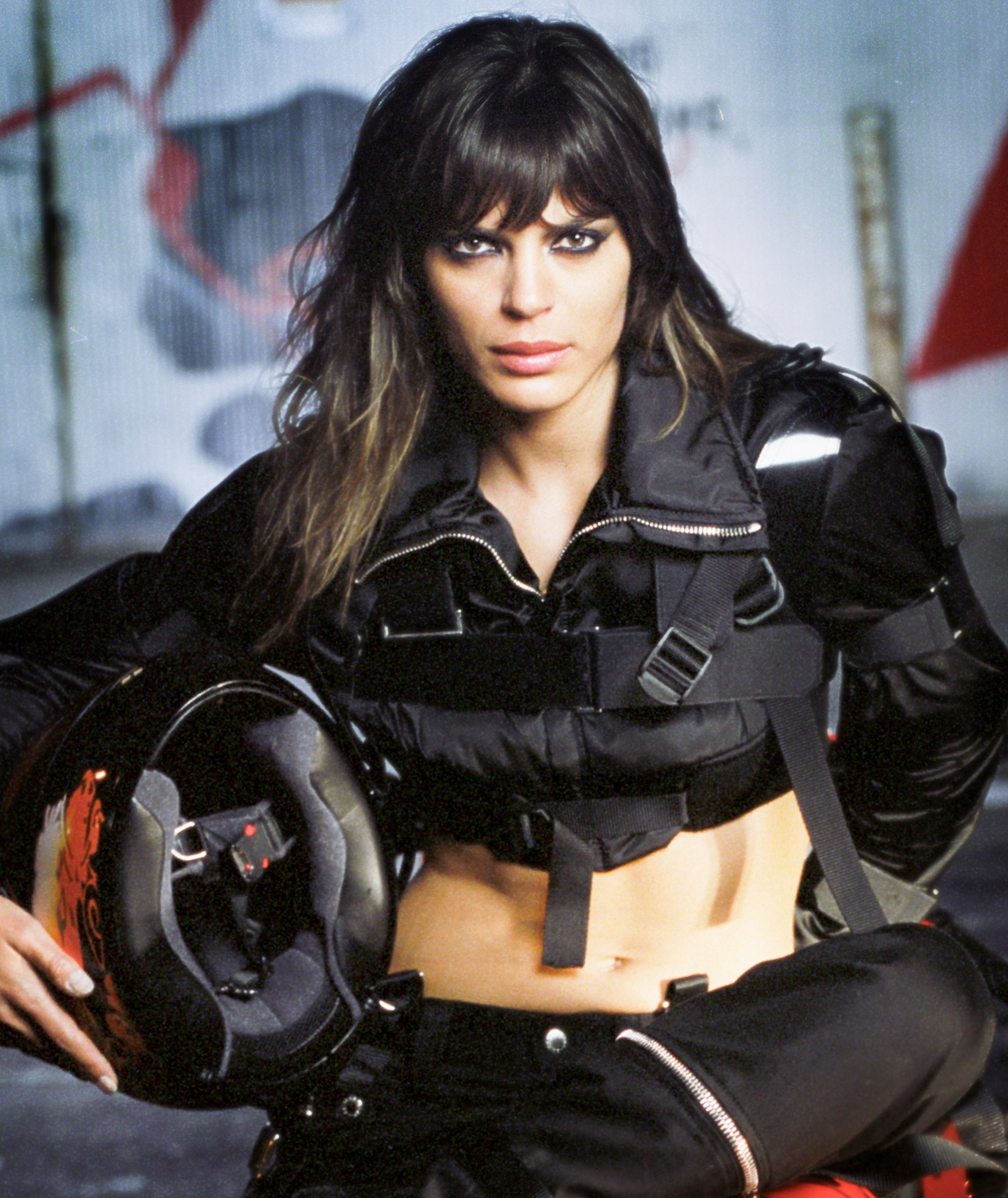 Editorial image of a model holding a motorcycle helmet during a photo shoot