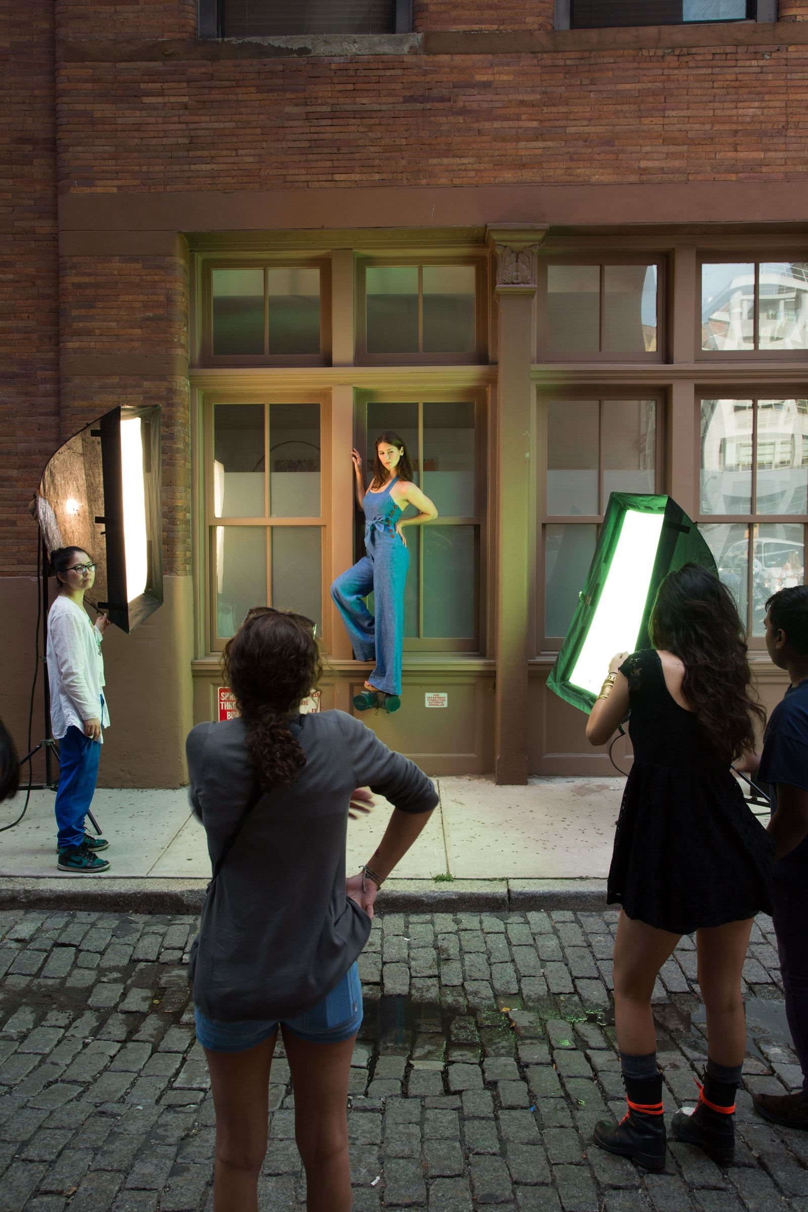 Photo shoot on the street with students holding lights on a model standing on a pipe.