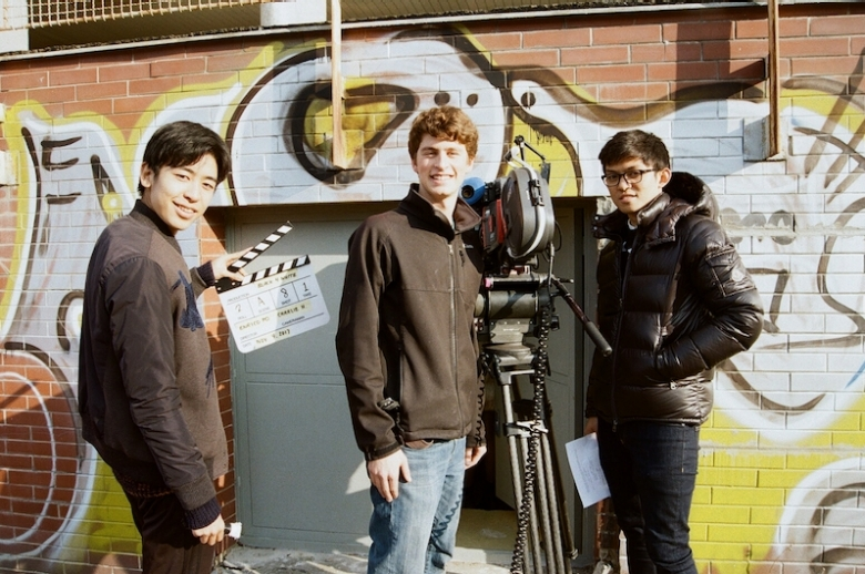 Film students on set with film equipment.