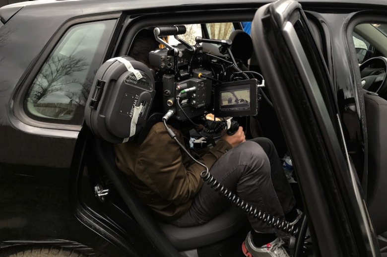 35mm camera and filmmaker seated in a car.