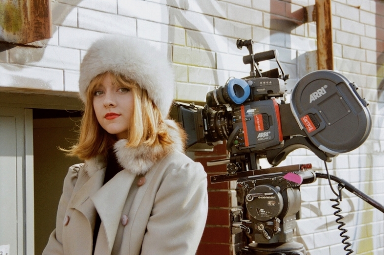 Young actress standing in front of a 35mm camera.