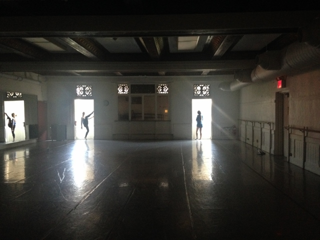 Three dancers backlit in the doorways of a dark dance studio.