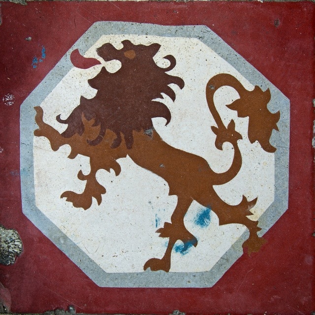 Lion painted on a white background and bordered in red on ceramic tile.