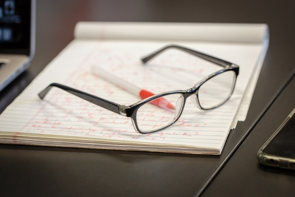 A pair of glasses set on top of a legal pad an red pen.