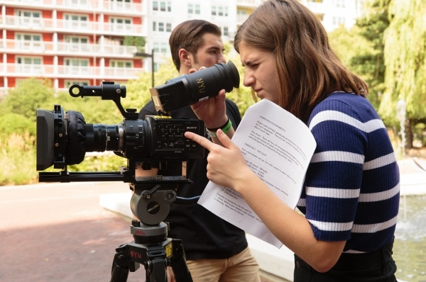 Student looking through a digital film camera at an outside shoot