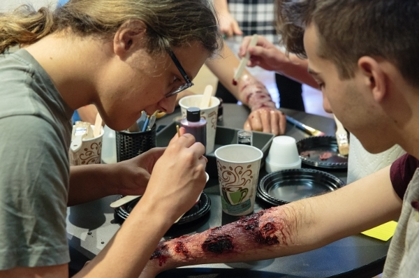 Student applying special effects makeup to another student's arm